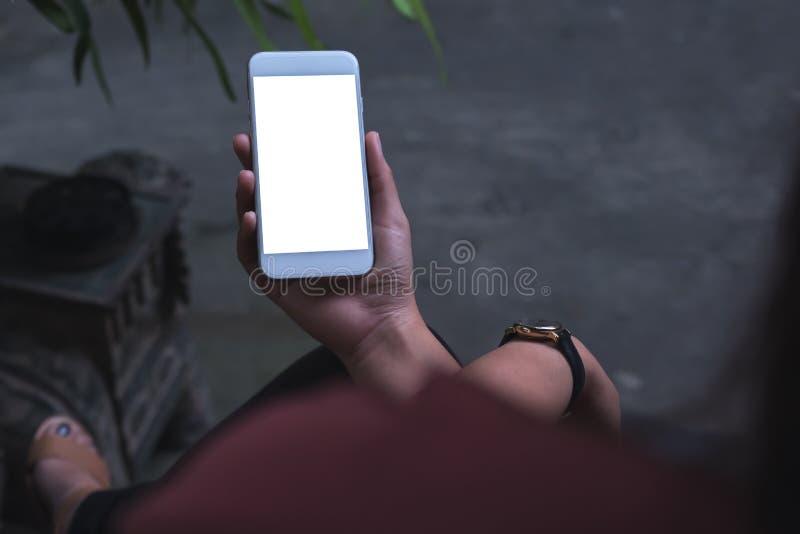 L'image de maquette d'une séance de femme a croisé la jambe et le téléphone portable blanc de participation avec l'écran vide ave images stock