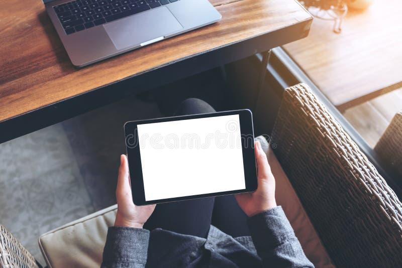 L'image de maquette du ` s de femme remet tenir le PC noir de comprimé avec l'écran blanc vide sur la cuisse avec l'ordinateur po photo libre de droits