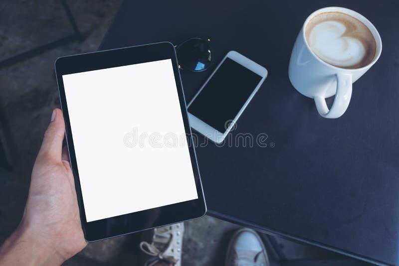 L'image de maquette de vue supérieure d'un ` s d'homme remet tenir le PC noir de comprimé avec l'écran blanc vide, tasse de café, photo libre de droits
