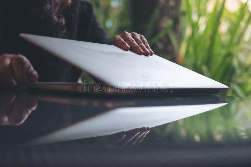 L'image de plan rapproché des mains du ` un s de femme d'affaires ferment et ouvrent l'ordinateur portable sur la table en verre  images stock