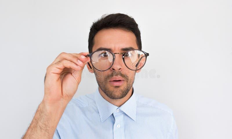 L'image de plan rapproché du jeune mâle beau européen étonné, regardant par des lunettes, des contacts bordent des verres, utilis photographie stock libre de droits
