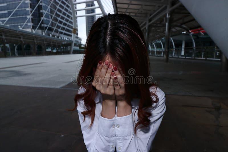 L'image discrète de la jeune femme d'affaires asiatique soumise à une contrainte frustrante avec des mains sur se sentir de visag image libre de droits