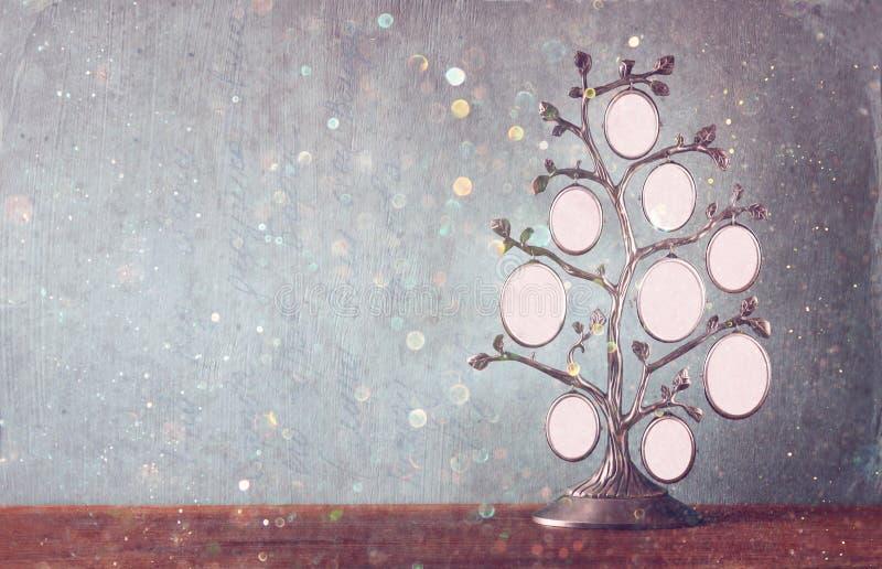 L'image du cadre classique d'antiquité de vintage de l'arbre généalogique sur la table en bois et le scintillement allume le fond images stock
