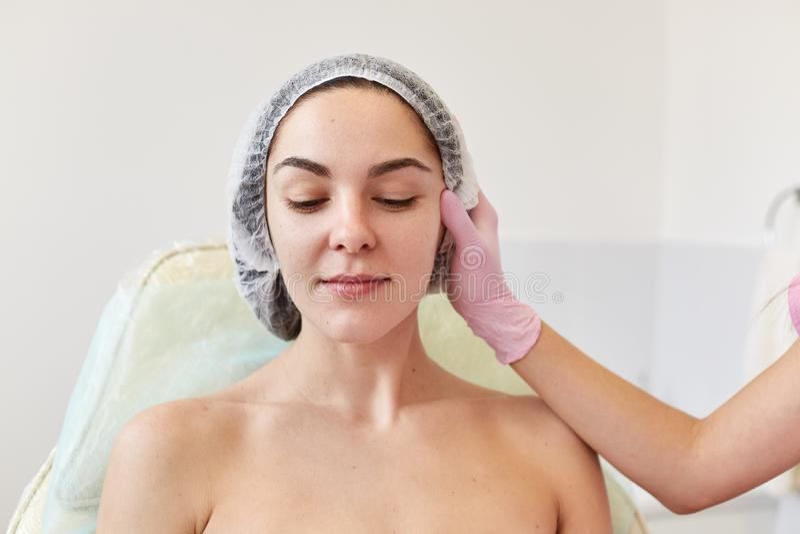 L'image du cosmetologist sans visage dans les gants médicaux roses au travail dans le salon de cosmétologie examine la femme atti photo stock