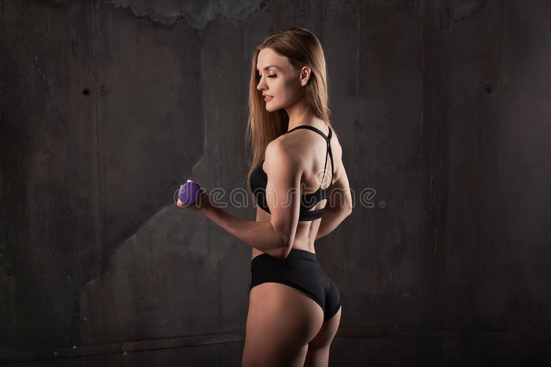 L'image du jeune athlète féminin musculaire portant l'usage noir de sport se tient avec le sien de nouveau à l'appareil-photo sur photos libres de droits