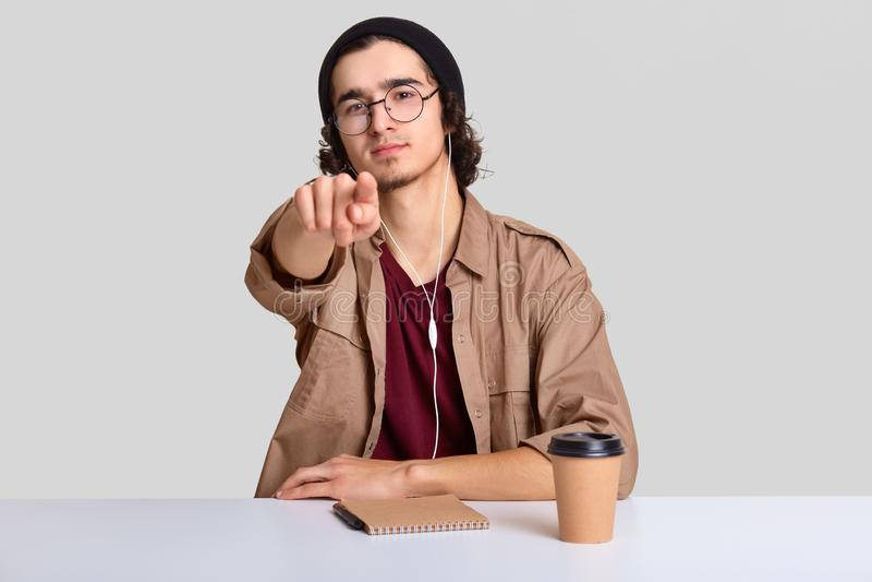 L'image du mâle attirant porte les lunettes rondes, se repose au bureau avec du café et l'organisateur, points directement à la c images libres de droits