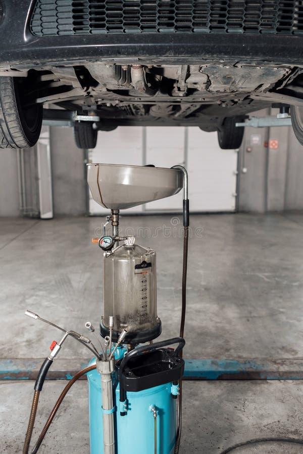 L'image du réservoir pour l'huile utilisée de carter La voiture sur l'ascenseur photo stock