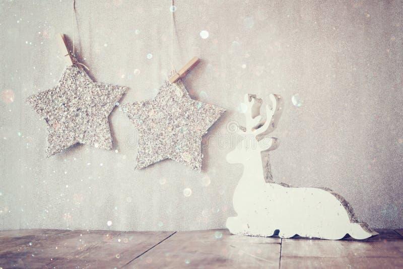 L'image du renne en bois blanc et du scintillement tient le premier rôle accrocher sur la corde au-dessus du fond d'argent de sci photographie stock