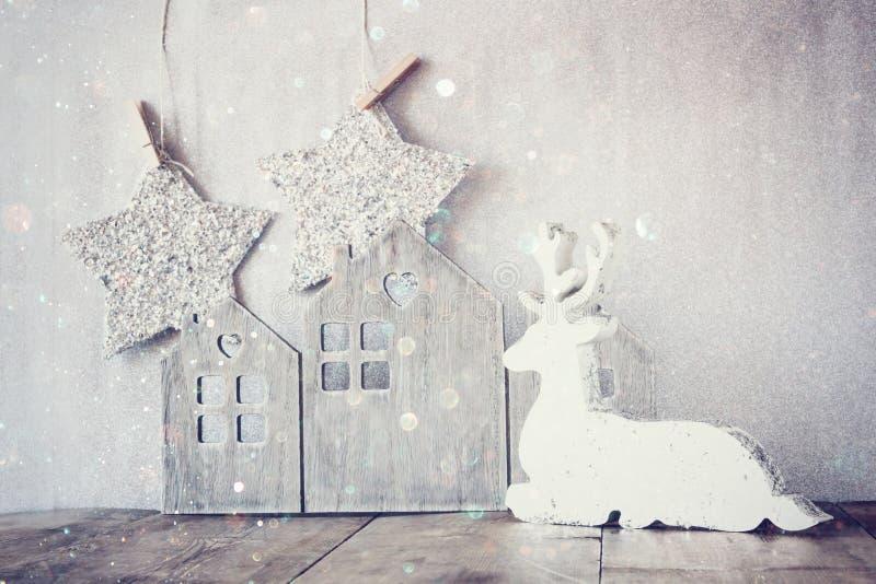 L'image du renne en bois blanc et du scintillement tient le premier rôle accrocher sur la corde au-dessus du fond d'argent de sci photo libre de droits