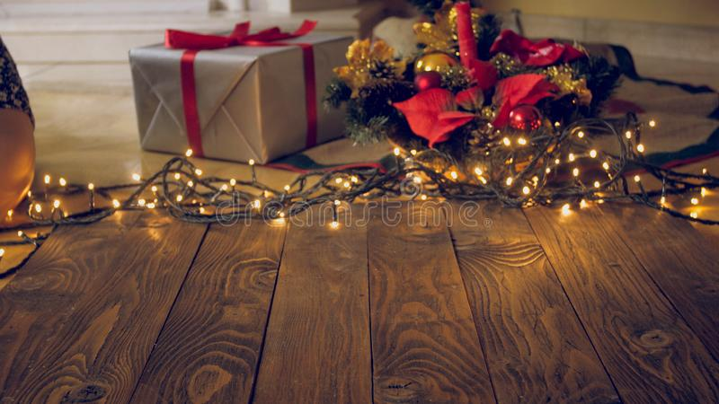 L'image modifiée la tonalité de vide woden des conseils avec les lumières de Noël rougeoyantes et des présents sur le backgorund image stock