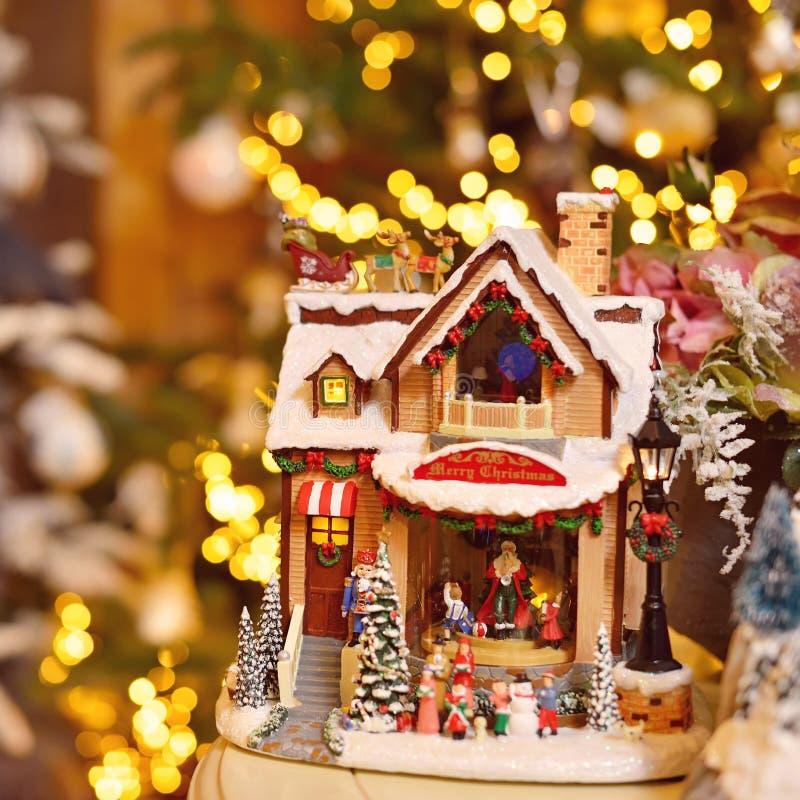 L'image modifiée la tonalité de vintage de la maison adorable de jouet de musique de Noël avec Santa miniature présente le fond d photographie stock