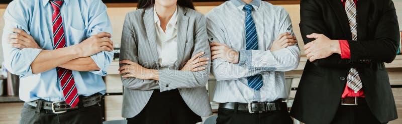 L'image panoramique de bannière d'une position créative d'équipe d'affaires avec des bras a croisé ensemble dans la ligne et le c images stock