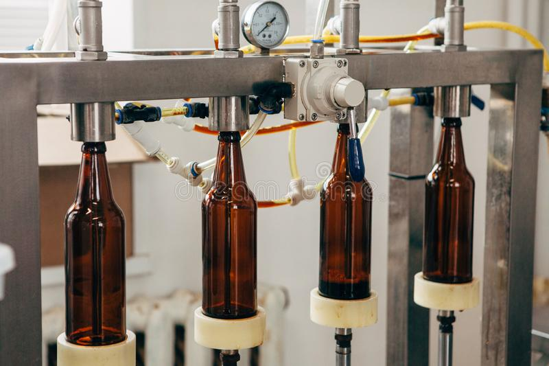 L'imbottigliatrice della birra per quattro imbottiglia una fabbrica di birra privata immagine stock