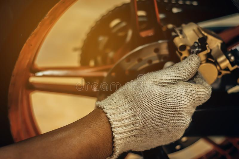 L'immagine è vicina su, la gente sta riparando un motociclo immagine stock libera da diritti