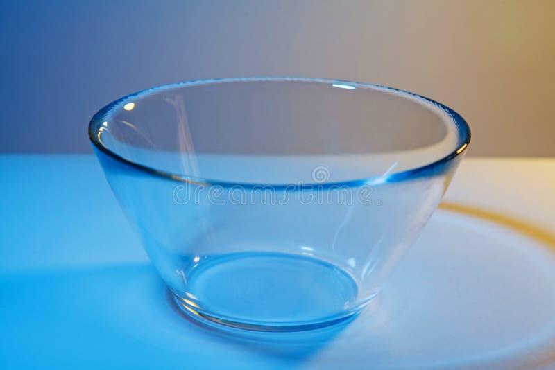 L'immagine astratta della ciotola di vetro trasparente semplice si è accesa da due luci nei colori di contrapposizione ultraviole immagini stock