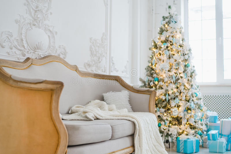 L'immagine calma del salone domestico di lusso interno ha decorato l'albero di Natale ed i regali, sofà coperto di coperta Fuoco  fotografia stock libera da diritti