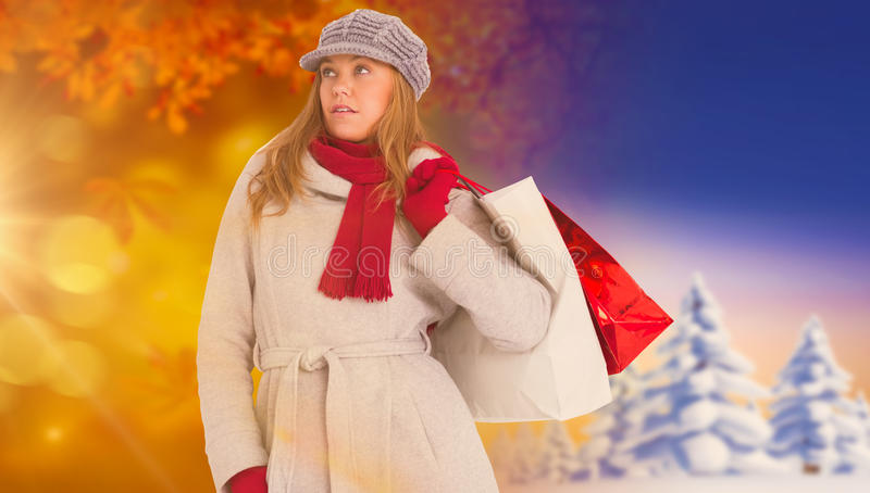 L'immagine composita della bionda felice nell'inverno copre la posa fotografia stock