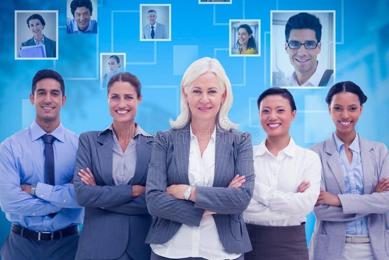 L'immagine composita della gente di affari con le armi ha attraversato sorridere alla macchina fotografica fotografie stock libere da diritti
