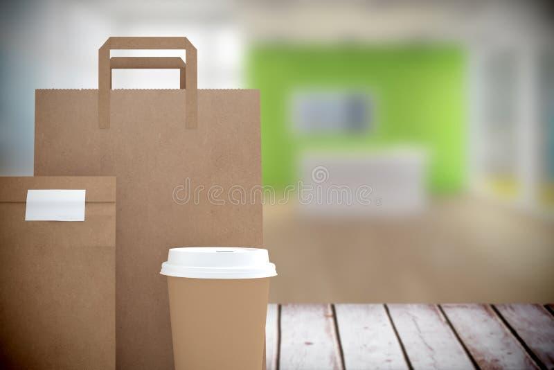 L'immagine composita della tazza di caffè eliminabile ed il pacchetto insaccano immagine stock