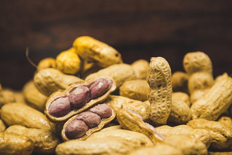 L'immagine d'annata di stile delle arachidi bollite si sbuccia fuori su fondo di legno fotografia stock