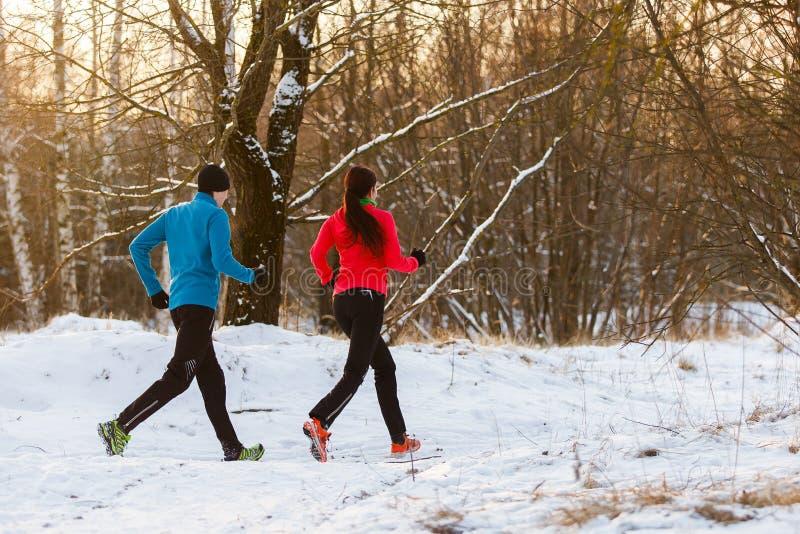 L'immagine dalla parte posteriore degli sport uomo e donna sulla mattina funziona nell'inverno fotografie stock