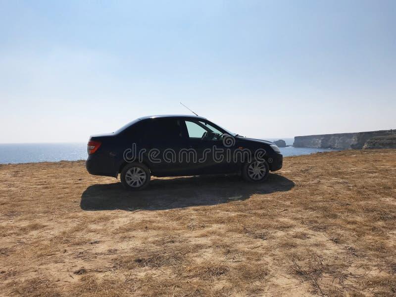L'immagine davanti alla scena dell'automobile sportiva dietro come il sole che va giù con i generatori eolici nella parte posteri fotografia stock