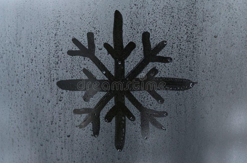 L'immagine del fiocco di neve è disegnata con un dito sulla superficie di una finestra di vetro appannata Frosty Weather immagini stock