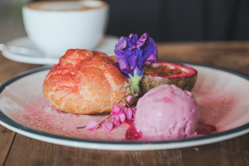 L'immagine del primo piano di un piatto dei Choux screma, gelato e frutto della passione rosa con la belle decorazione e tazza di immagini stock libere da diritti
