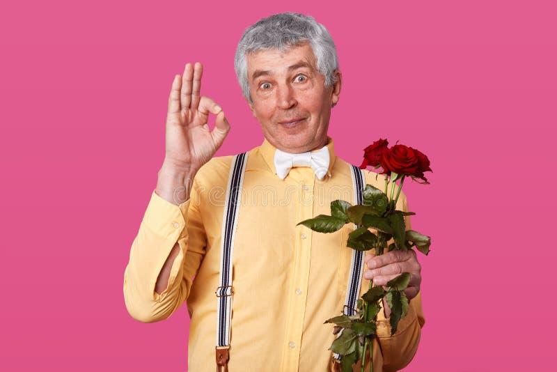 L'immagine del segno bello di approvazione di rappresentazione dell'uomo senior, pronta a andare alla datazione, tiene i fiori ro immagine stock