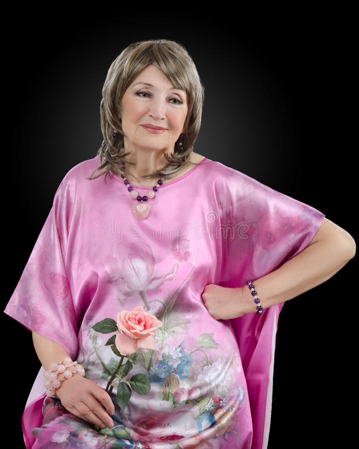 L'immagine della donna di 76 anni pensierosa ha sull'abito di seta rosa immagine stock