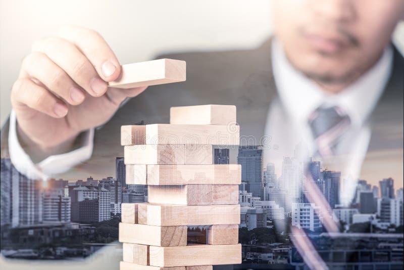 L'immagine della doppia esposizione dell'uomo d'affari indica uno dei mattoni della costruzione sulla sovrapposizione della torre immagini stock
