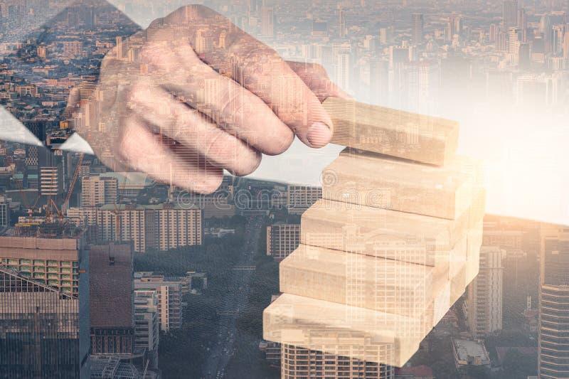 L'immagine della doppia esposizione dell'uomo d'affari indica uno dei mattoni della costruzione sulla sovrapposizione della torre immagine stock