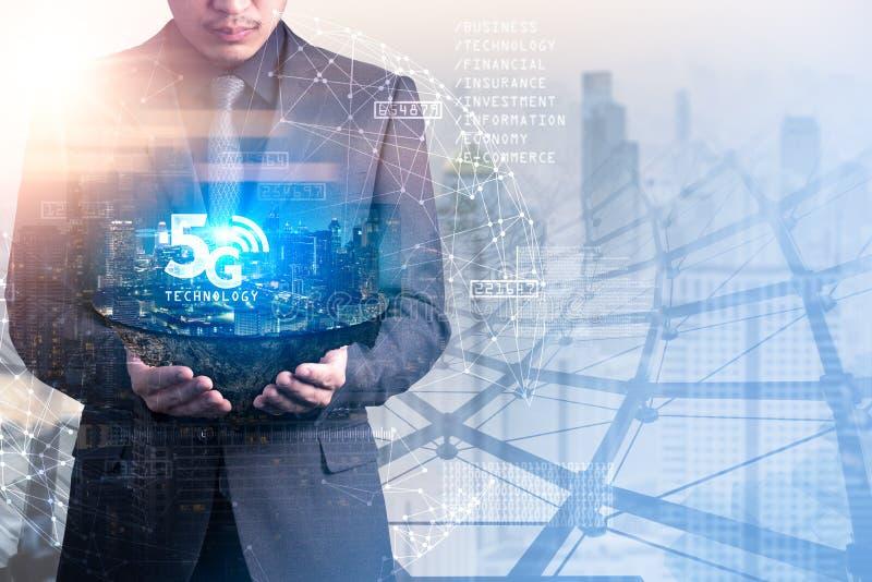 L'immagine della doppia esposizione dell'uomo d'affari tiene la sovrapposizione dell'isola di paesaggio urbano con l'ologramma 5G fotografia stock