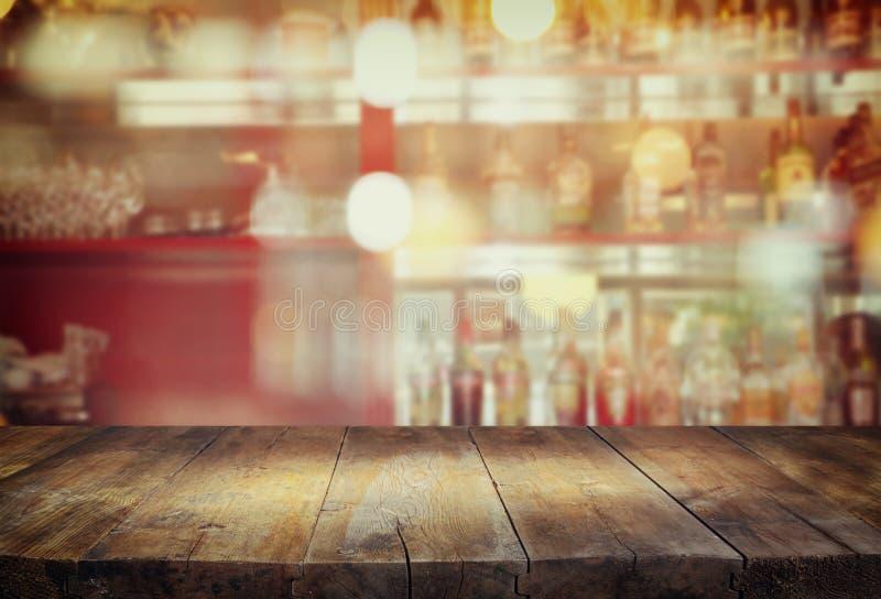 L'immagine della tavola di legno davanti all'estratto ha offuscato il fondo delle luci del ristorante immagini stock