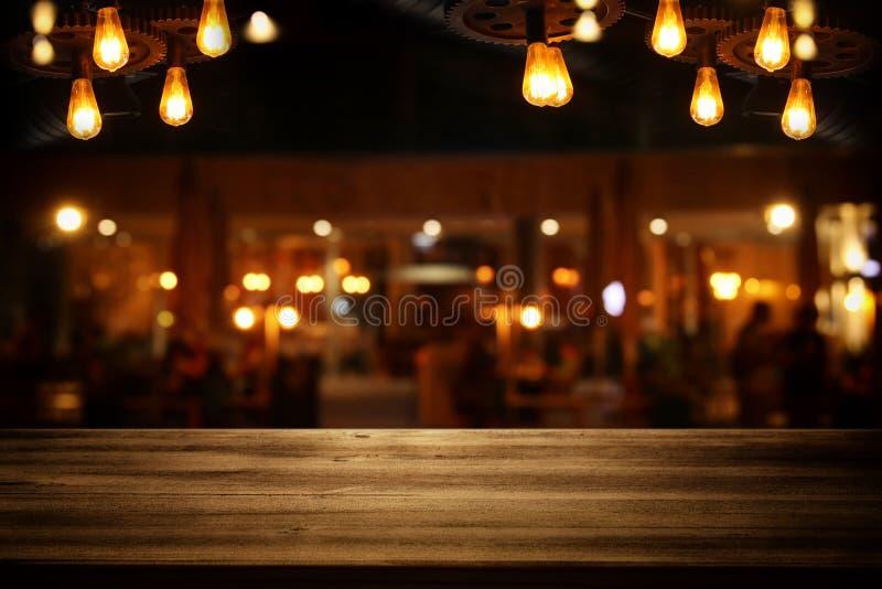 L'immagine della tavola di legno davanti all'estratto ha offuscato il Li del ristorante immagine stock
