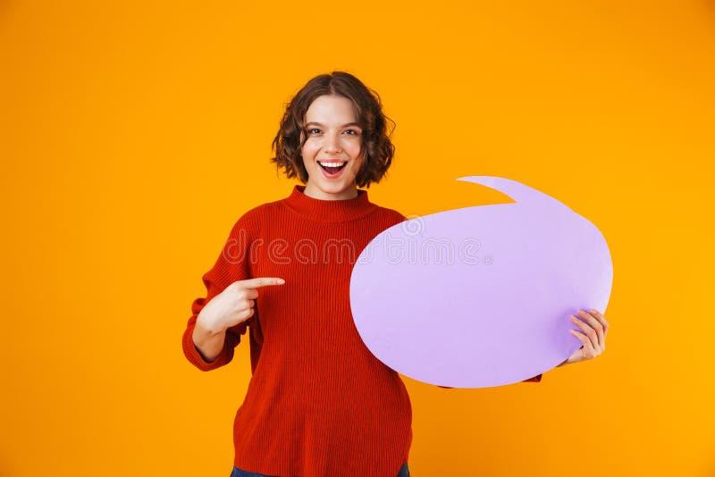 L'immagine della tenuta gioiosa della ragazza ha pensato la bolla con copyspace mentre stava isolata sopra fondo giallo fotografia stock