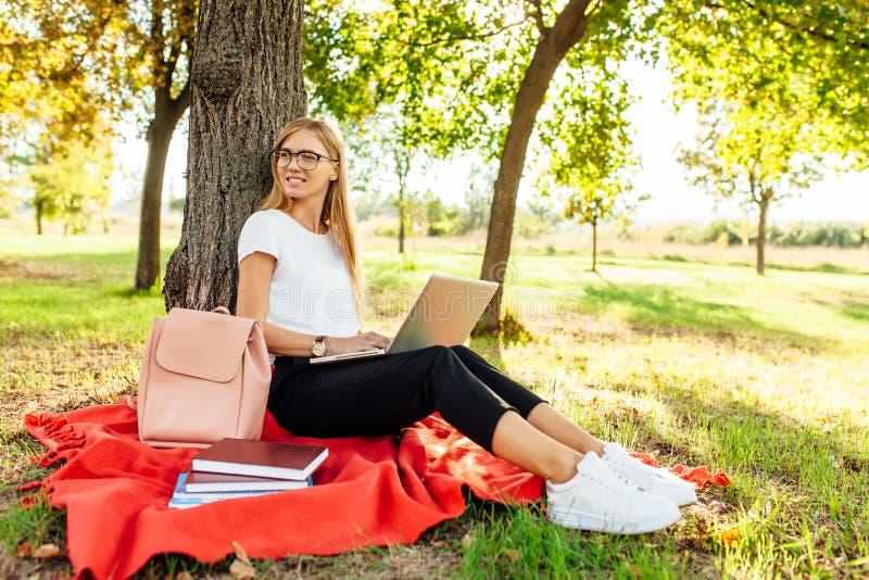 L'immagine di bella studentessa con i vetri, che lavora sopra fotografia stock