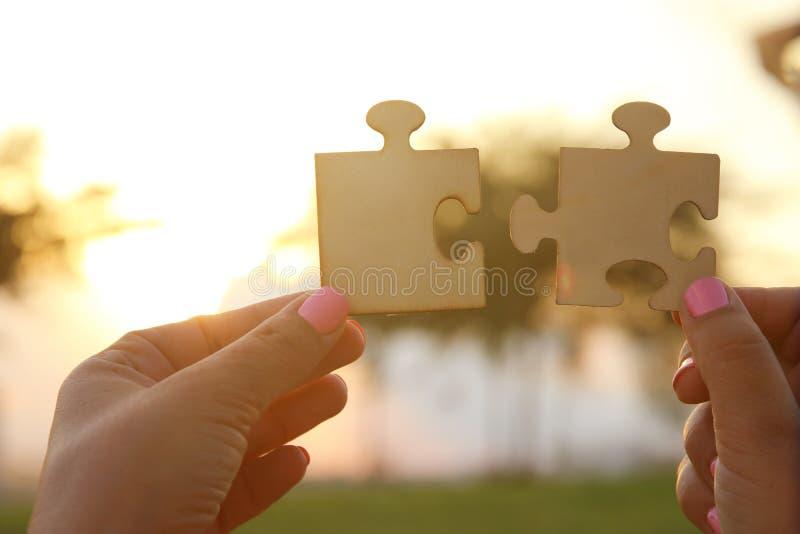 L'immagine di concetto di una donna passa a tenuta due pezzi di puzzle davanti al sole tempo di tramonto con il chiarore della le immagini stock