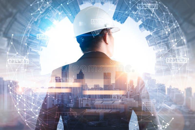 L'immagine di doppia esposizione dell'ingegnere che sta indietro durante la sovrapposizione di alba con l'immagine di paesaggio u fotografia stock