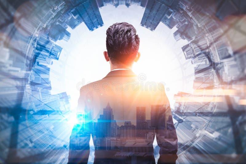 L'immagine di doppia esposizione dell'uomo di affari che sta indietro durante la sovrapposizione di alba con l'immagine di paesag immagini stock