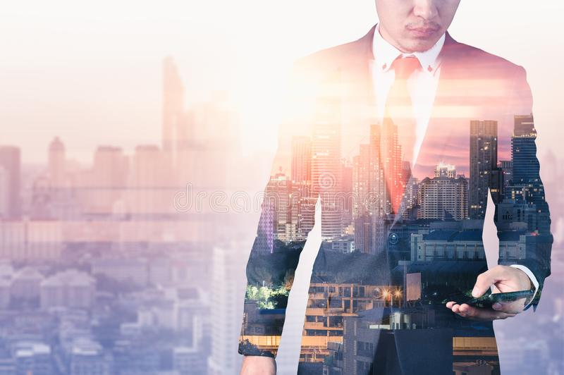 L'immagine di doppia esposizione dell'uomo d'affari facendo uso di uno smartphone durante la sovrapposizione di alba con l'immagi fotografia stock libera da diritti