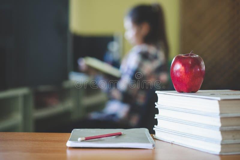 L'immagine di tema della scuola che comprende una mela e un mucchio i libri i precedenti è uno studente che si siede leggendo un  fotografia stock