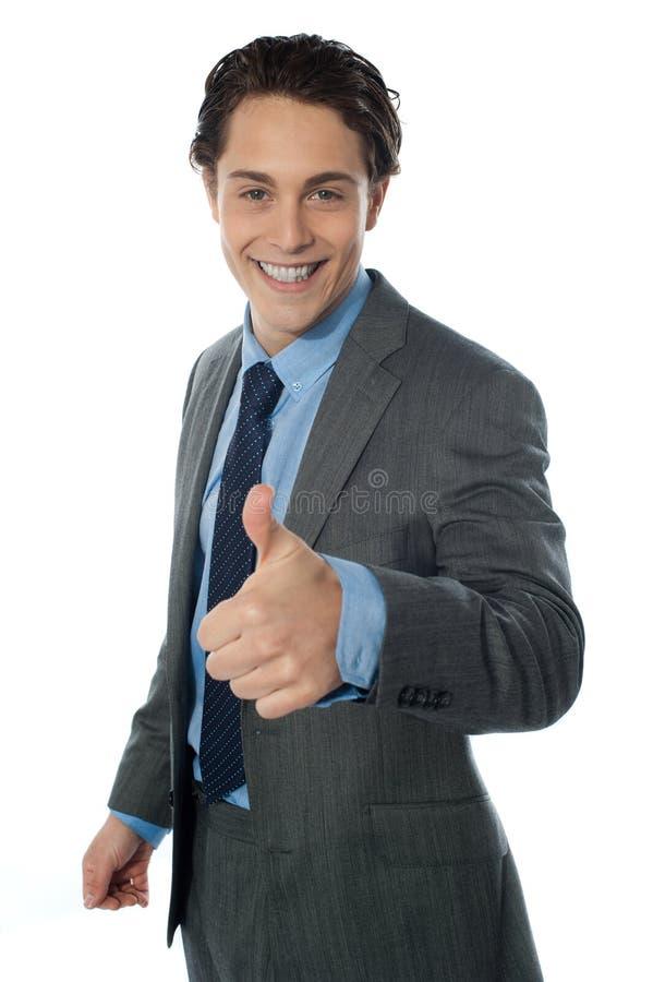 L'immagine di un uomo corporativo con i pollici aumenta il segno fotografia stock libera da diritti