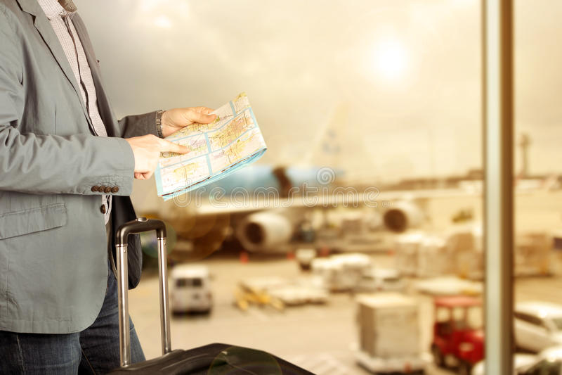 L'immagine di una fine sull'uomo sta cercando le direzioni sulla mappa nell'aeroporto fotografie stock