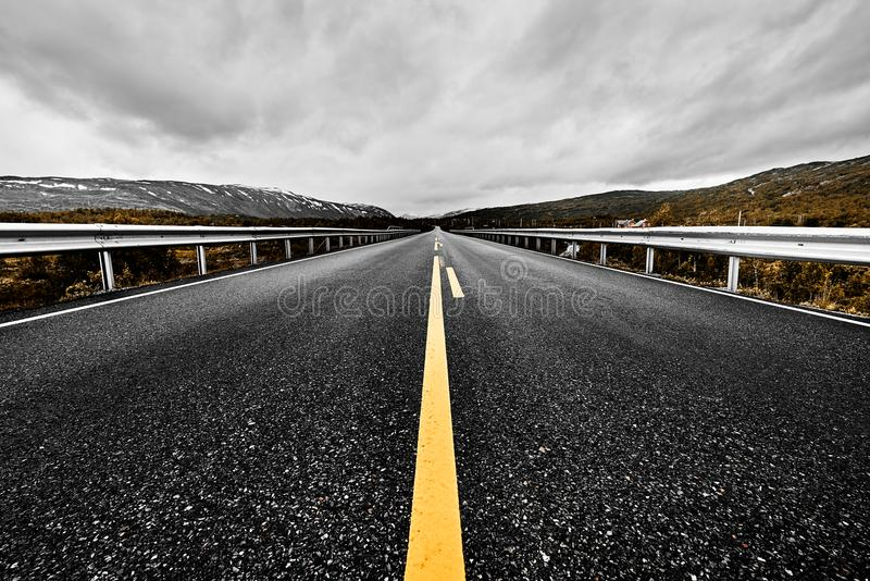 L'immagine di una prateria spalancata e delle montagne con una strada pavimentata della strada principale che allunga fuori fino  fotografia stock