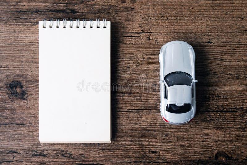 L'immagine di vista superiore del taccuino della pagina in bianco e la piccola automobile modellano sul immagine stock