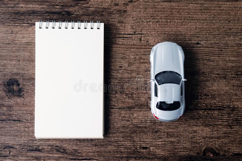 L'immagine di vista superiore del taccuino della pagina in bianco e la piccola automobile modellano sul immagini stock