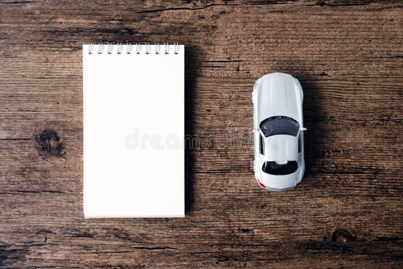L'immagine di vista superiore del taccuino della pagina in bianco e la piccola automobile modellano sul fotografia stock
