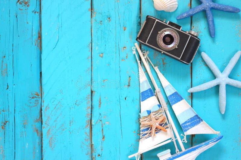 L'immagine di vista superiore della macchina fotografica della foto, la barca di legno, le conchiglie e la stella pescano sopra l immagine stock