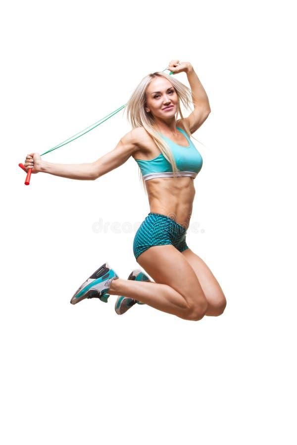 L'immagine integrale di un giovane mette in mostra la donna che salta sul salto della corda sopra fondo bianco immagine stock